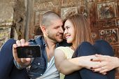 Young Couple In Embrace Takes Selfie