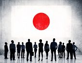 Group of business people standing with a view of the national flag of Japan.