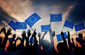 Group of People Waving European Union Flags in Back Lit