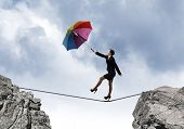 Young businesswoman walking on rope above gap with colorful umbrella