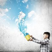 Young boy splashing colorful paint from bucket