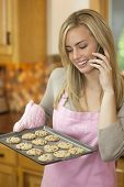 Woman Baking Cookies And Talking On Phone