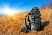 backpack on dry autumn grass in mountain meadow