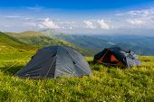 Two tourist tents among green meadow in mountains