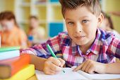Calm schoolboy looking at camera while drawing at lesson