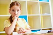 Portrait of pensive girl looking at camera at lesson of reading