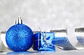 Christmas ball and curly decorative ribbon on bokeh background