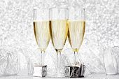 Glasses of champagne and christmas gifts on silver background