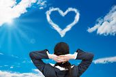 Businesswoman Looking At Heart Shaped Cloud In Sky