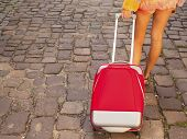 Young girl's legs and red suitcase on the pavement road, travel concept.