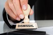 stock photo of unemployed people  - Closeup of hand holding rubber stamp with Dismissal sign at table in office - JPG