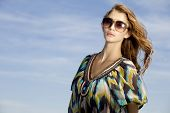 portrait of young adult beautiful and attractive brunette woman in sunglasses on background blue sky