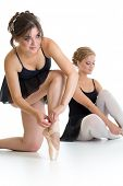 Two beautiful young girls preparing for dance training together isolated