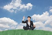 Businessman sit on grassland and finger toward the sky.