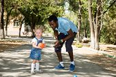 Young African American God Father With  Little Girl Playing Football On Nature At Summer. Use It For