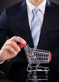 Businessman With Shopping Cart Model At Desk