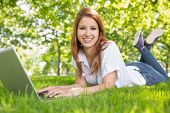 Smiling redhead using laptop in the park on a sunny day