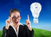 Composite image of young businesswoman getting an idea against cloud light bulb