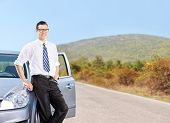Happy young man standing by a car on an open road