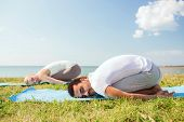 fitness, sport, friendship and lifestyle concept - smiling couple making yoga exercises on mats outd