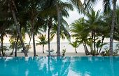 vacation, beach, summer and leisure concept - swimming pool on tropical beach