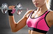 fitness, sport, exercising and people concept - close up of sporty woman with heavy steel dumbbells
