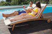 Romantic young couple with drinks sitting by swimming pool