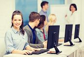 education, techology and internet concept - group of smiling students with computer monitor looking