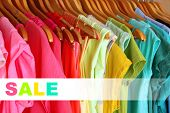 Concept of discount. Colorful clothes on hangers in wardrobe