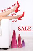 Concept of discount. Beautiful female legs in red shoes on sofa with shopping bags