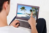 Man Looking At Beach Photo On Laptop In Living Room