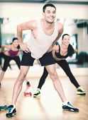 fitness, sport, training, gym and lifestyle concept - smiling male trainer working out in the gym