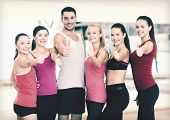 fitness, sport, training, gym and lifestyle concept - group of happy people in the gym showing thumb