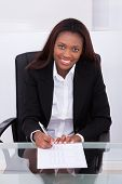 Confident Businesswoman Filling Form At Desk In Office