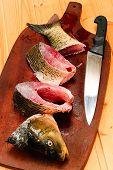 Raw Carp Fish  On A Wooden Cutting Board