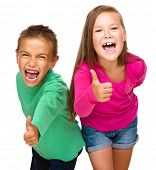 Little boy and girl are showing thumb up sign, isolated over white