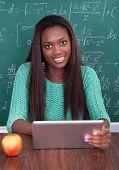 Teacher Holding Digital Tablet At School Desk