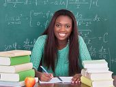 Confident Female Teacher Writing In Book At Classroom Desk