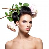 Beautiful young woman with pink flowers in hair - isolated on white.