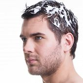Close-up portrait young handsome man washing hair with shampoo - isolated on white.