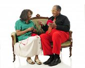 A senior man happily looking at his wife as he hold the yard as she begins a crochet project.  On a white background.