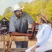 A mature African American cowboy flirting with a sitting woman over a fence in an old west town.