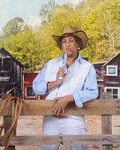 A mature African American Cowgirl in an old western town, blowing smoke off her gun.