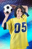 A beautiful teen girl in an over-sized jersey,happily holding a soccer ball behind her head.