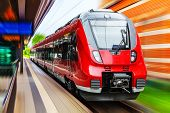 picture of passenger train  - Scenic summer view of modern high speed passenger commuter train on tracks at the station platform with motion blur effect - JPG