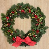 Christmas and winter wreath with red bow, holly, ivy, mistletoe, spruce fir and pine cones over oak