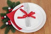 Christmas dinner place setting with white plates, cutlery, red bow ribbon, fir and bauble decoration