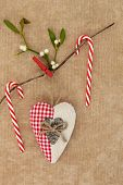 Heart shaped christmas decoration with candy canes and mistletoe over old oak brown paper background