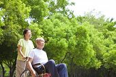 foto of wifes  - Asian senior man sitting on a wheelchair with his wife - JPG