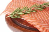 fresh raw red fish fillet on wooden plate and rosemary